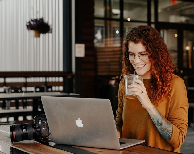 woman casual coffee mac laptop orange top