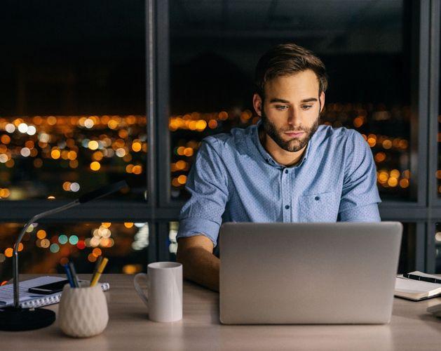 man laptop night time office